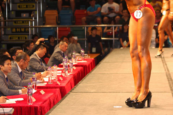 A panel of judges score a competitor at the 2012 Hong Kong Bodybuilding Championships.  Photo ©istolethetv.  Retrieved from Flickr under creative commons: https://creativecommons.org/licenses/by/2.0/legalcode