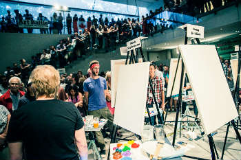 Each artist is allowed to prepare a pallet of paints before the timer begins, and they gather in the centre to start the competition. [Photo courtesy of Art Battle Canada]