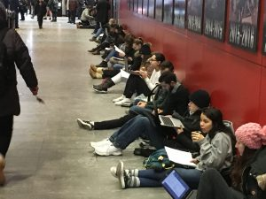 Students sitting in the hall outside the exam room with their computers open
