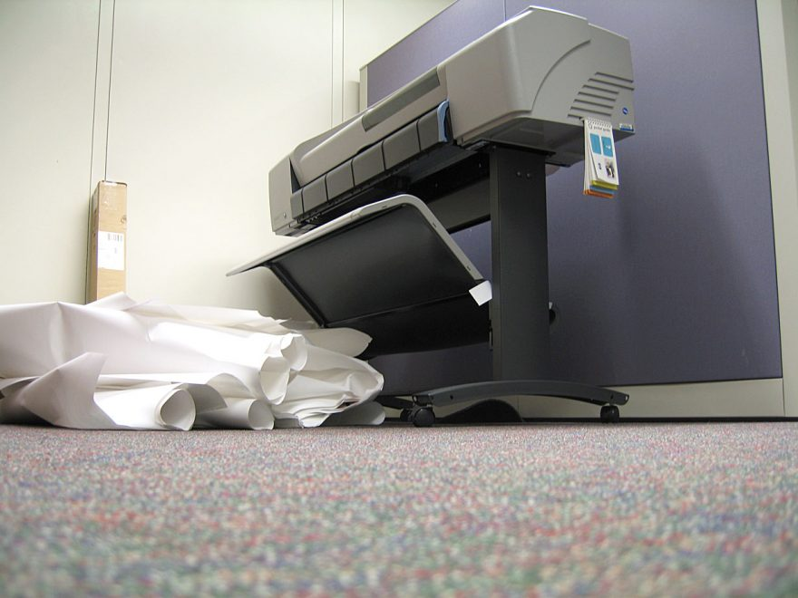a printer with paper on the floor